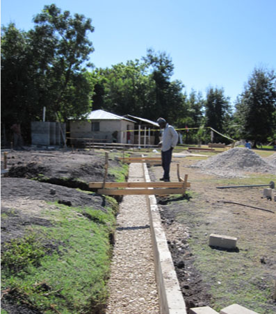 Bachi inspecting the gravel filled trench in Deslandes, Haiti.